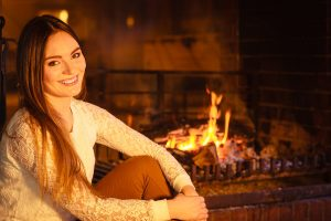 bigstock-Happy-Woman-Relaxing-At-Firepl-101837213