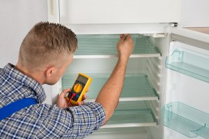 bigstock-Technician-Checking-Fridge-Wit-98038526