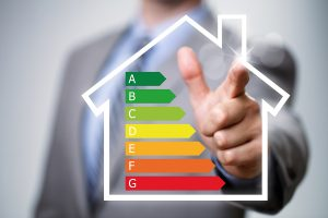 Businessman pointing to energy efficiency rating chart and house